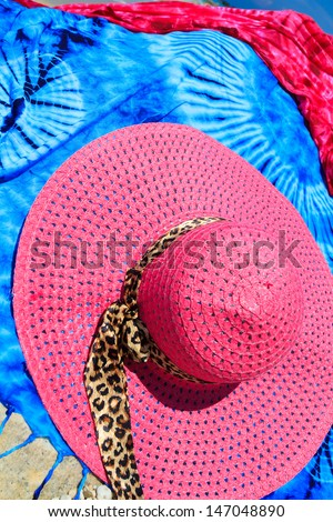 Sarong and straw hat on the beach - stock photo