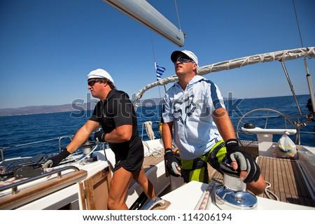 "SARONIC GULF, GREECE - SEPTEMBER 24: Unidentified sailor participates in sailing regatta ""Viva Greece 2012"" on September 24, 2012 on Saronic Gulf, Greece. - stock photo"