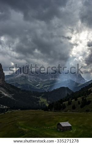 Sassolungo (Langkofel) under the clouds with a ray of light on Gardena valley, Dolomites, Italy