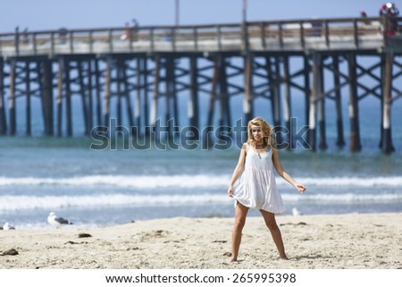 Sassy blonde woman dancing on the beach in a summer white dress - stock photo