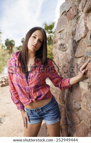 Sassy young teen girl posing in tied red flannel shirt and denim shorts - stock photo