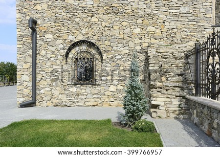 SATANOV KHMELNYTSKIY, UKRAINE-CIRCA SEPTEMBER, 2015: The synagogue of the sixteenth century restored to a quincentenary. Fragment of stone wall with buttress, decorative grill and metallic wrought fence