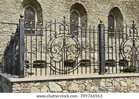 SATANOV KHMELNYTSKIY, UKRAINE- CIRCA SEPTEMBER, 2015: The synagogue of the sixteenth century restored to a quincentenary. Fragment of wrought ornamented decorative artistic fence on stone foundation