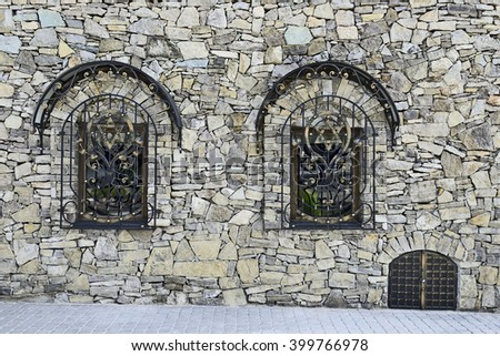 SATANOV KHMELNYTSKIY, UKRAINE- CIRCA SEPTEMBER, 2015: The synagogue of the sixteenth century restored to a quincentenary. Stone wall with two windows with decorative wrought grills and emergency exit