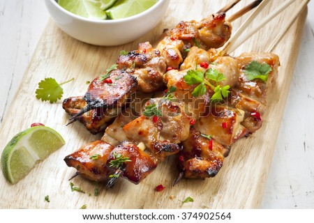 Satay chicken skewers with lime and chili. - stock photo