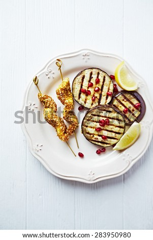 Satay skewers with grilled aubergine and pomegranate seeds - stock photo