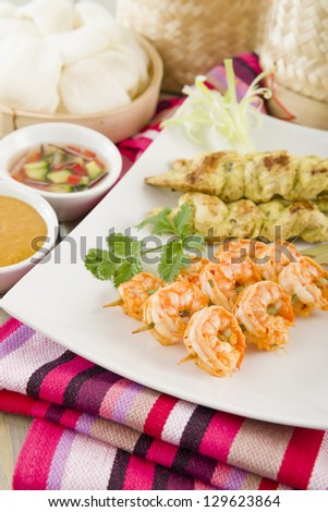 Sate Gai & Sate Goong - Thai chicken and prawn satays served with cucumber and onion relish, peanut sauce and prawn crackers. - stock photo