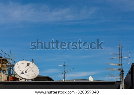 satellite and antenna on the roof - stock photo