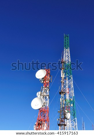 Satellite and communication towers against blue sky, vertical image.