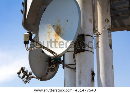 Satellite antenna on the pillar with blue sky