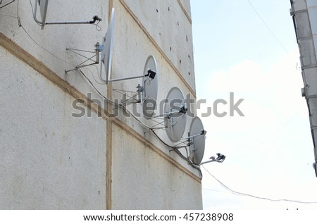 Satellite antenna on the wall - stock photo
