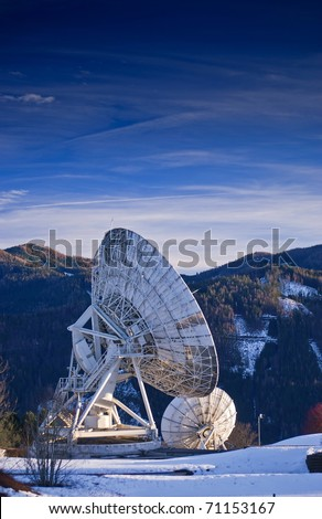 Satellite broadcasting dish at sunset time with mountains in background. - stock photo