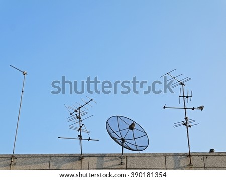 Satellite dish and many antennas with blue sky on top roof with bird in city. - stock photo