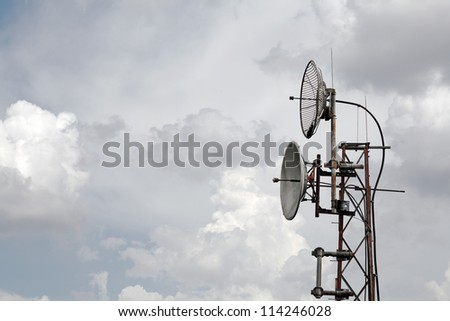 Satellite dish and radio antennae mounted on a metal telecommunication tower against a cloudy sky.