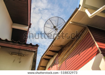Satellite dish antenna for television on house roof with blue sky background, in countryside, Thailand.