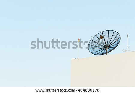 Satellite dish antenna mounted on rooftop in urban area on clear blue sky - stock photo