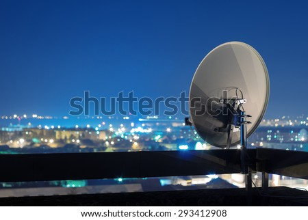 Satellite dish antenna on top of the building in urban area at night. - stock photo
