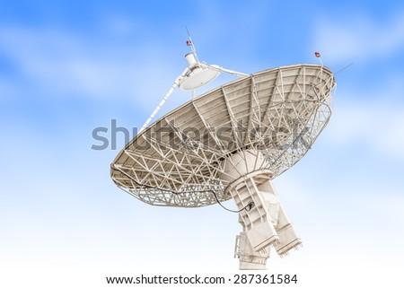 satellite dish antenna radar big size isolated on blue sky background - stock photo