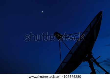 Satellite dish in evening sky - stock photo