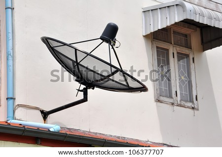 Satellite dish is attached to the wall of the house