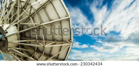 satellite dish on blue sky background - stock photo