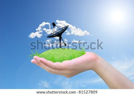 satellite dish on green grass in women hand - stock photo