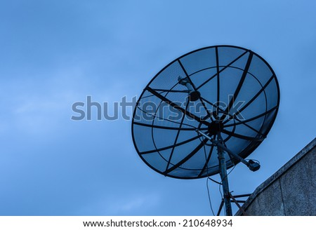 Satellite dish on top of old building.