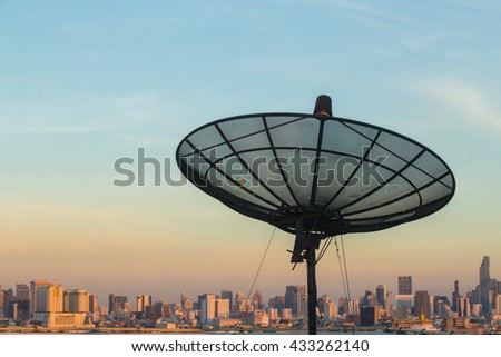 Satellite dish on top of the building on evening - stock photo