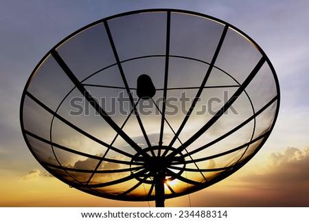 Satellite dish on twlight sky background - stock photo