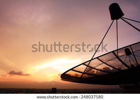 Satellite dish silhouette on twilight sky background - stock photo