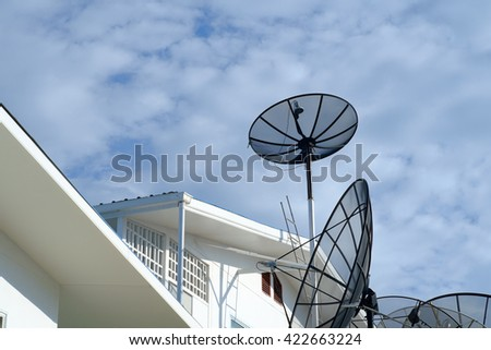 Satellite dish transmission data on blue sky background
