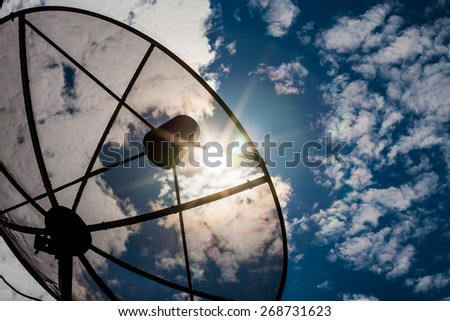 Satellite dishes communication technology network with sun and white cloud in background