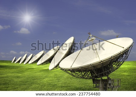 Satellite dishes line in wide meadow with clouds in blue sky in sunny day - stock photo