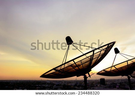 Satellite dishes on twilight sky background - stock photo