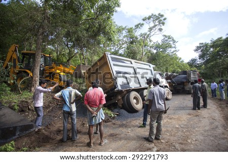 Sathyamangalam, Tamil Nadu, India - June 24, 2015: An excavator goes to lift a truck that has gone off the road, people watch on