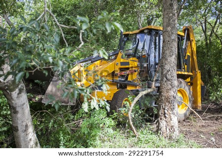 Sathyamangalam, Tamil Nadu, India - June 24, 2015: An excavator is seen parked among trees in the Sathyamangalam forest - stock photo