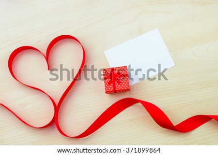 Satin ribbon in the shape of a heart on wood background , box for rings. Valentines Day