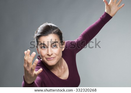 satisfaction and smile concept - happy 30s brunette expressing excitement and fun with theatrical body language - stock photo