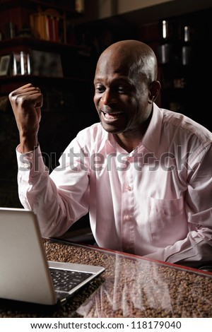 Satisfied african man in pink shirt gesturing and shouting at laptop - stock photo