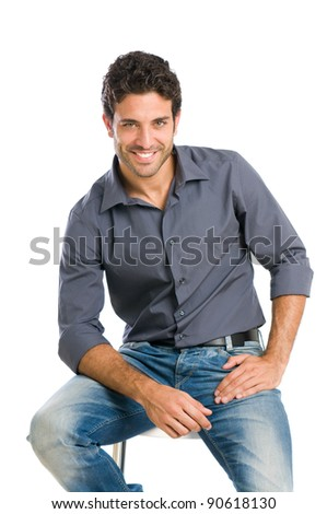 Satisfied and proud young man sitting on chair and looking at camera isolated on white background - stock photo