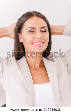 Satisfied and relaxed. Happy young businesswoman in suit holding hands behind head and smiling
