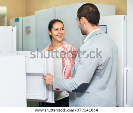 Satisfied beautiful couple looking at large fridges in domestic appliances section
