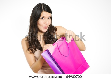 Satisfied beautiful young female customer with her purchase held in a purple recyclable paper shopping bag smiling happily at the camera, isolated on white with copy space
