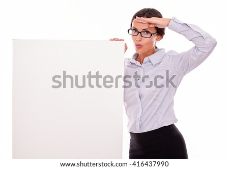 Satisfied brunette businesswoman with glasses looking at the camera, holding a placard, wearing her straight hair tied back and a button down shirt, gesturing with her left hand on her brow - stock photo