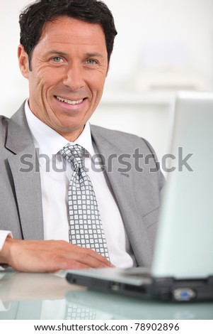 Satisfied businessman in front of laptop computer - stock photo