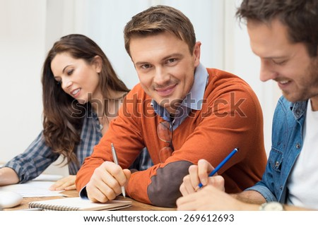 Satisfied Businessman looking at camera with other workers sitting at meeting table