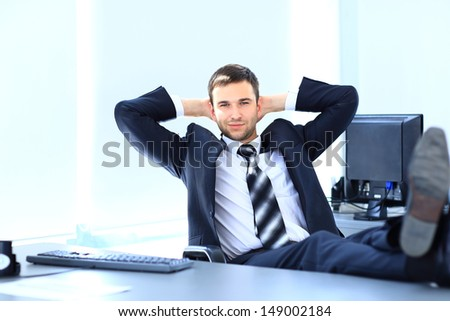 Satisfied businessman relaxing in his office - stock photo