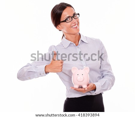 Satisfied businesswoman holding pink porcelain piggy bank while smiling and looking at the camera and wearing her hair back in a button down shirt with a thumb up gesture on a white background - stock photo