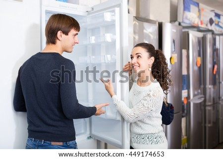 Satisfied customers choosing fridges in domestic appliances section