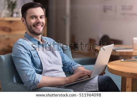 Satisfied handsome man smiling and using laptop.